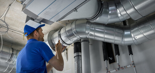 hvac worker install ducted pipe system for ventilation and air conditioning. copy space