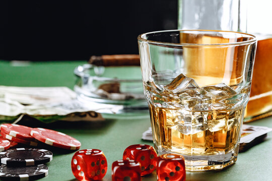 Glass of whiskey, cigar, playing cards and chips on green background