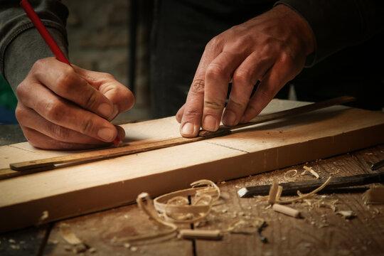 Carpenter measuring and marking wood in workshop
