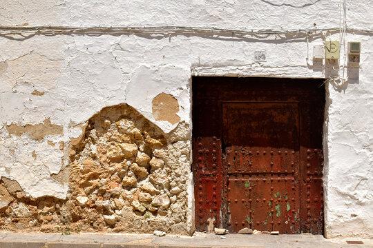 Old doors. Old wooden door, in the ruined façade of a street, located in a town of Castilla la Mancha, in Spain
