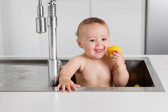Happy baby taking bath in kitchen sink holding rubber duck