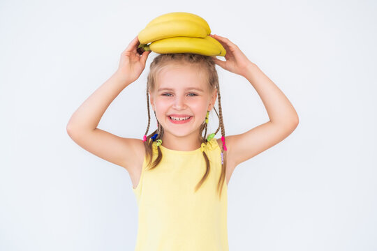 Cute smiling girl with banana in yellow