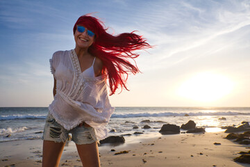 Fototapeta Carefree fit body girl in casual style fashion enjoys her holidays at tropical paradise beach. Happy red-haired woman on travel vacation. Relax, fun, and enjoy summer vacation concept obraz
