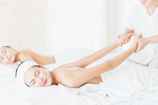 Happy female lying on stomach on massage table getting back spa treatment. Happy young woman receiving massage at spa. Staff stretching their bodies to customers.