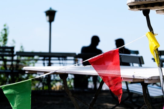 silhouette of couple sitting behind flags on chair at table in front of coastline