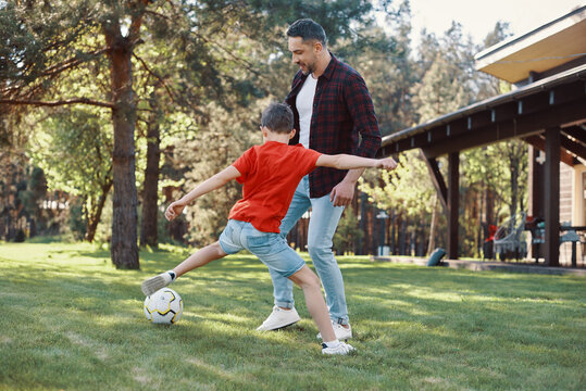 Happy father and son playing football and smiling while having fun on the backyard