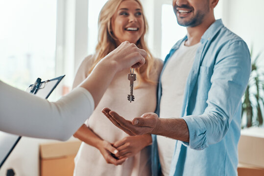 Young beautiful couple in casual wear smiling and embracing while receiving keys from new home