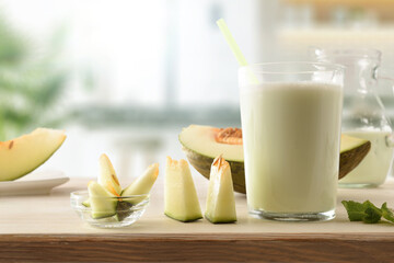 Obraz Glass with melon milk shake on bench in kitchen front - fototapety do salonu