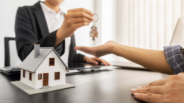 Real estate agent holding a key and asking costumer for contract to buy, get insurance or loan real estate or property.