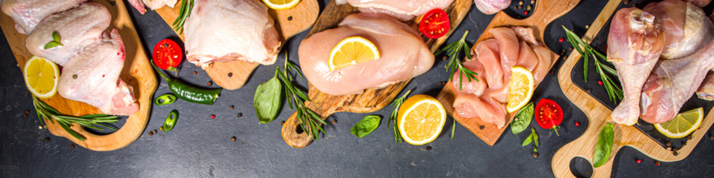 Various raw chicken meat portions. Set of uncooked chicken fillet, thigh, wings, strips and legs on black cooking table background with spices