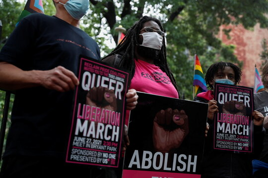 People wearing protective face masks gather during a press conference condemning NYPD brutality during Pride Month at the Stonewall Memorial Park in New York City