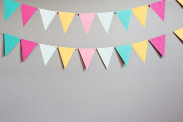 Colorful party flags over cement concrete gray wall texture background, pastel birthday colored flags with copy space Holiday concept