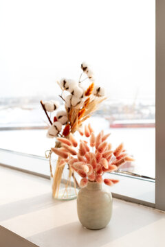Dried flowers next to the window where there is a bright light.