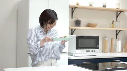 Fototapeta 完成した料理を持つ若い女性 obraz