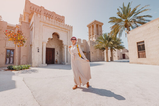 Woman tourist wearing red turban and biege long dress walks through the old narrow streets of Bur Dubai and Creek. Travel and sightseeing concept