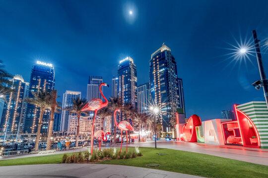 24 February 2021, Dubai, UAE: Popular tourist attraction - decorative statues of pink flamingos in modern district of Dubai Creek marina harbor