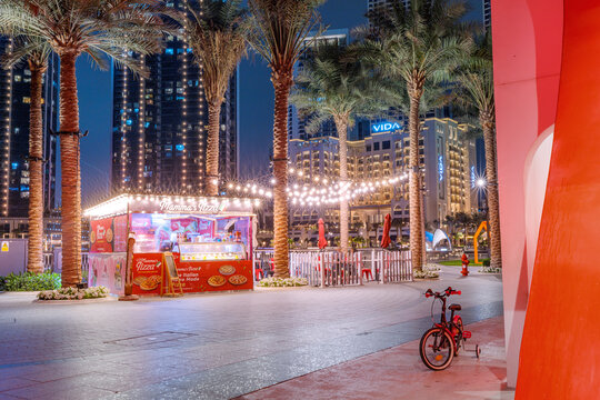 24 February 2021, Dubai, UAE: People buy delicious Pizza fastfood at a kiosk stall at evening with lights