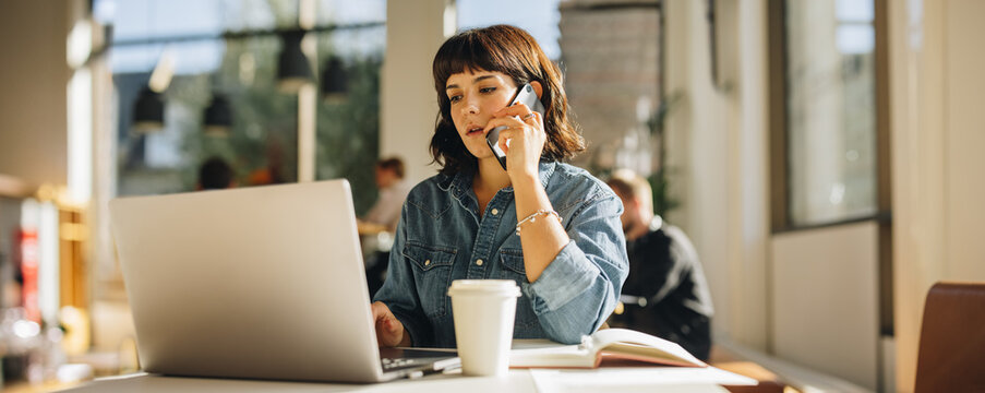 Businesswoman talking on cell phone in coworking space