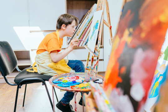 Education and special child concept. Special needs boy training to draw at art therapy studio.