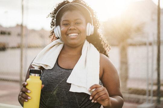 Sport curvy black girl listening music with headphones - Focus on face