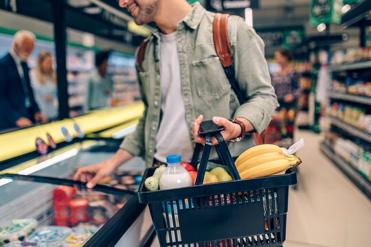 Young man buying groceries at the supermarket. Other customers in background. Consumerism concept.