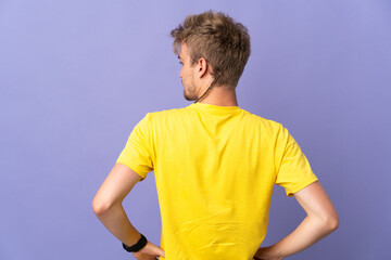 Young handsome blonde man isolated on purple background in back position and looking side - fototapety na wymiar