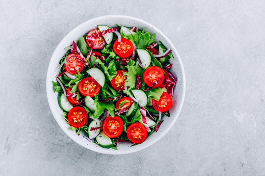 Green salad bowl with tomatoes, cucumbers, red onions, radicchio and fresh lettuce.