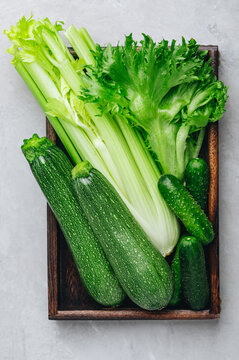 Assorted green vegetables with celery, cucumbers, zucchini and fresh lettuce in a wooden crate