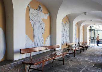Obraz NOWY SACZ, POLAND - MAY 28, 2021: A monastery corridor decorated with reliefs of saints - fototapety do salonu