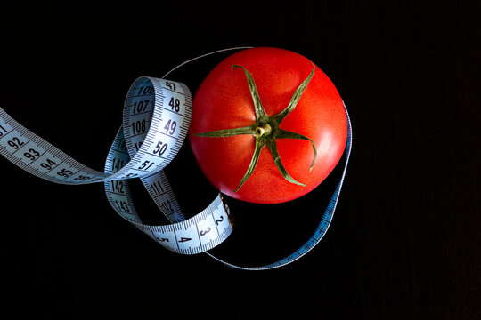 Tomato and a blue meter tape on a black background, concept of healthy eating and nutrition