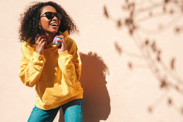 Beautiful black woman with afro curls hairstyle.Smiling hipster model in yellow hoodie. Sexy...