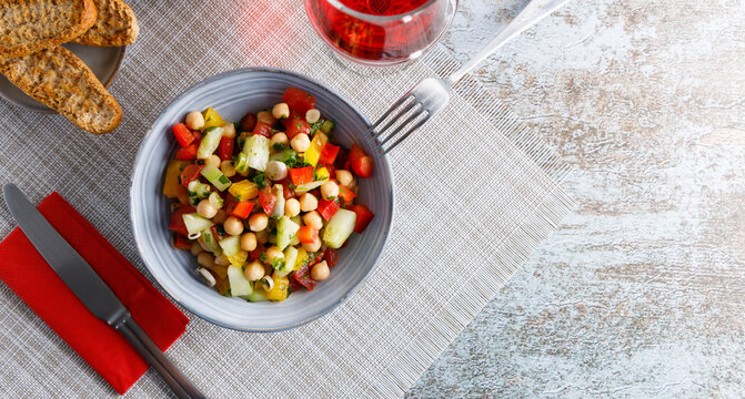 Homemade chickpea salad. Homemade healthy vegan salad, with chickpea , tomato, cucumber, paprika served in a bowl. Healthy meal, on a dinner table.