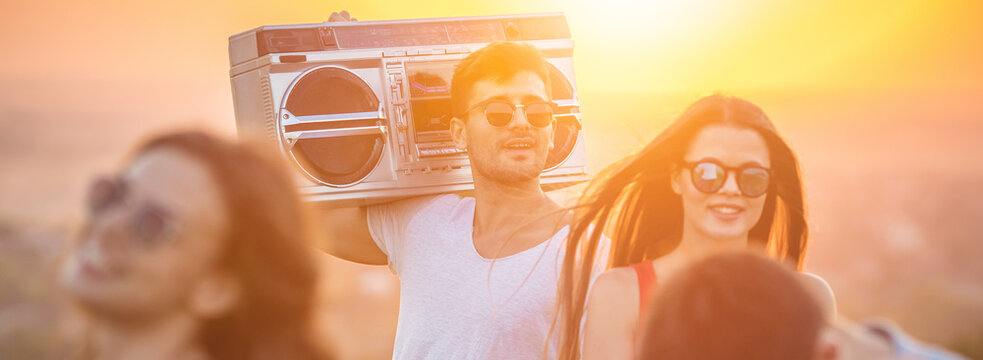 The happy people dancing with a boom box on the bright sun background