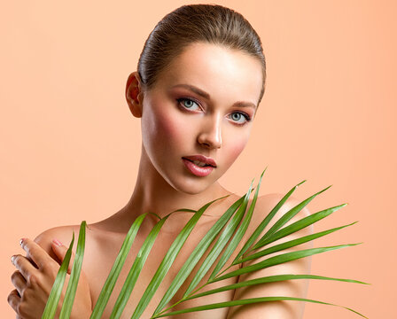 White woman with healthy skin of body and palm leaves. Tanned body of an attractive girl with green plants. Large palm leaves cover the breast.