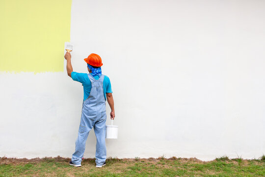 Rear view of painter man painting outdoor the wall,  isolated on big empty space