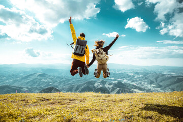 Obraz Hikers with backpacks jumping with arms up on top of a mountain - Couple of young happy travelers climbing the peak - Family, travel and adventure concept - fototapety do salonu