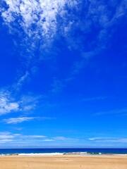 Krajobraz plaży z niebieskim niebem i chmurami oraz żółtym piaskiem.