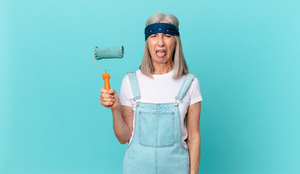 middle age white hair woman feeling disgusted and irritated and tongue out with a roller painting a wall