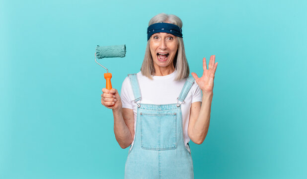 middle age white hair woman screaming with hands up in the air with a roller painting a wall