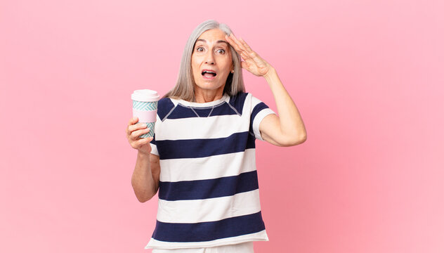 middle age white hair woman looking happy, astonished and surprised and holding a take away coffee container