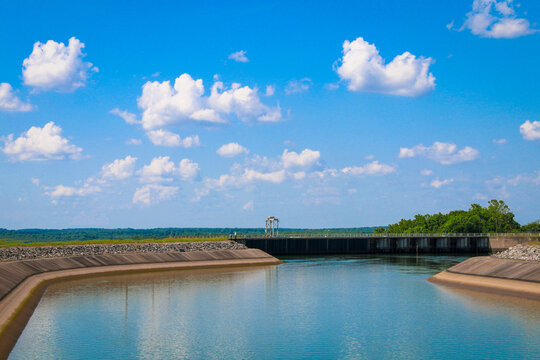 river dam water reservoir lake with surrounding walls and bright blue sunny sky and clouds reflection