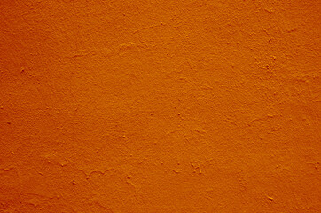 Old peeling paint on the wall. Red abstract background.Background from orange, stucco. Beautiful orange textured stucco on the wall