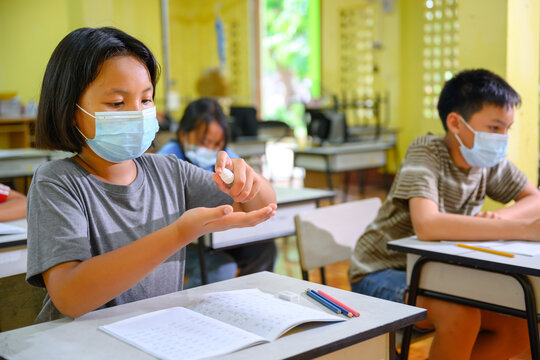 Asian elementary school students wear a protective mask Coronavirus (COVID 19) in classrooms at rural schools and washing hands by spraying alcohol or hand sanitizer.