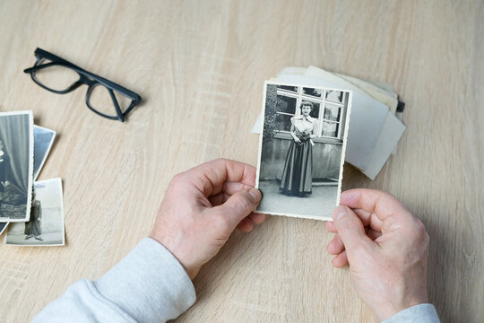 closeup male hand holding old vintage photos of 1940-1950, glasses on the table, concept of family tree, genealogy, childhood memories, memory of ancestors
