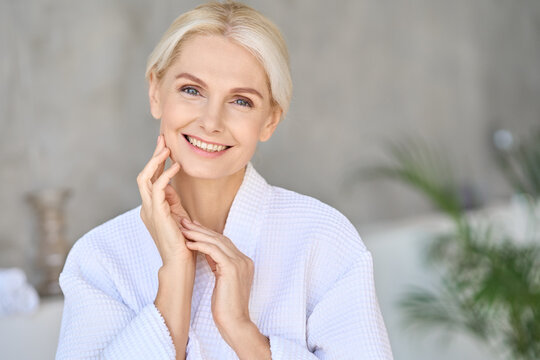 Headshot of happy smiling beautiful middle aged woman wearing bathrobe at spa salon hotel looking at camera touching face. Wellness spa procedures advertising. Skincare concept.