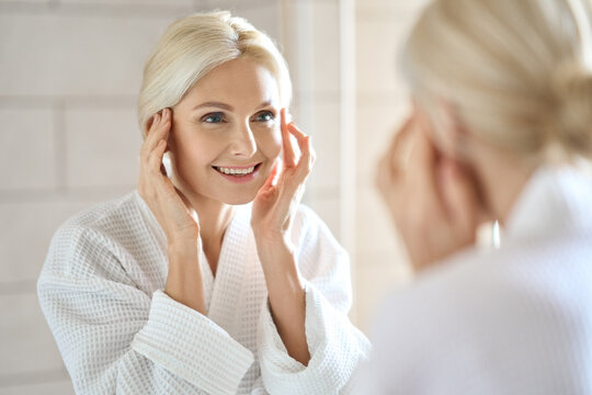 Gorgeous mid age adult 50 years old blonde woman standing in bathroom after shower touching face, looking at reflection in mirror smiling doing morning beauty routine. Older dry skin care concept.