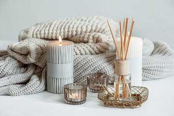 Obraz Cozy home composition with candles, aroma sticks and a knitted element. - fototapety do salonu