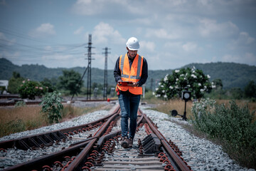 Fototapeta Engineer under  inspection and checking construction process railway switch and checking work on railroad station .Engineer wearing safety uniform and safety helmet in work. obraz