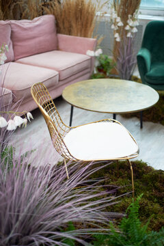 A golden chair with a mesh back stands on the moss. Eco design.Stylish interior with cereals and dried flowers.
