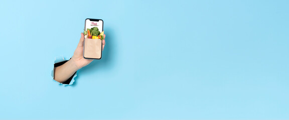 Fototapeta Woman hand showing smartphone using food delivery online mobile application order on internet over blue banner background. Panoramic image obraz